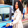 Image of Black Woman Opening a Blue Ford Escort
